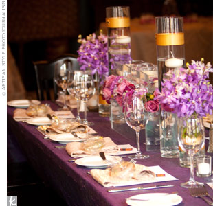 Varied flower arrangements, some filled with water and floating candles, topped the purple tables.