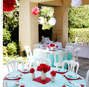 A big driveway at a private residence was transformed into a courtyard for the party. The planners strung paper pom-poms above a table and used oversized balloons to divide the spaces.