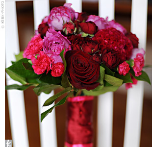 To complement the bright pink-and-red color scheme, the bride carried Yves Piaget roses and deep burgundy spray roses with contrasting hot-pink mini carnations and gloriosa lilies. A dark red ribbon and pearl accent accessorized the bouquet.
