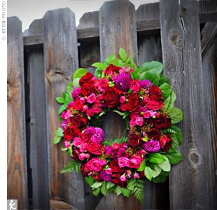 A wreath of vibrant red and pink blooms hung from the wooden garden gate and added a pop of color to the natural surroundings.
