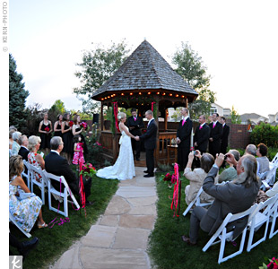Carrie and Nick said their vows in the bride's parents' backyard with the setting sun behind them. The couple stood before a gazebo covered in lush garlands, flowers and lots of pink and red ribbon. Vases filled with roses and carnations hung from shepherd's hooks along the stone walkway.
