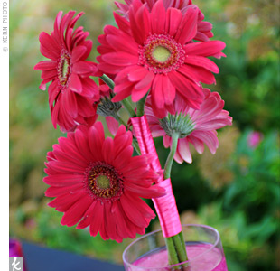 For a little bling on the reception tables, the florist filled various shaped vases with pink glass pebbles to hold up loosely wrapped pink and red gerbera daisies.