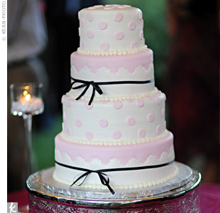 Fun pink fondant dots, pearls and black accents gave dimension to the four-tiered, multi-flavored wedding cake.