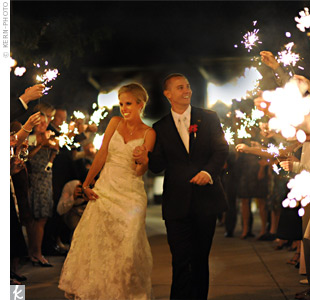 "Carrie and Nick left the celebration through a tunnel of glowing sparklers. ""It was very cool, and some of my favorite pictures from the wedding are of that scene,"" says Carrie."