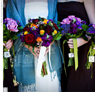 The warm colors of the season and the mountain view inspired the bouquets. Rich jewel-toned roses differentiated the bride's bouquet from the bridesmaids' purple blooms.
