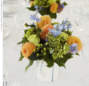 Orange, blue, and green flowers were arranged in ironstone pitchers for the centerpieces. Guests sat family-style at long tables to add to the casual atmosphere.