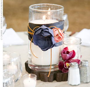 Glass containers and hurricane candles alternated with floral centerpieces on the 10 reception tables. The candles were wrapped with handmade fabric flowers, leather, and orchids.