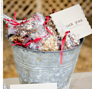 Lia didn't want her guests to have to worry about traveling with favors, so she and Mark made chocolate almond toffee from a recipe she got from a San Francisco bakery. Mark's sister and step-mother helped the couple package the toffee into the small cellophane bags tied with red grosgrain ribbon, and Lia printed and punched the edges of the cards.
