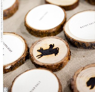 The place cards were a creative DIY project. Lia's mom cut the circular place cards from fallen pine branches found in the bride's grandparents' yard in Camino, CA and printed the guests' names on the front. The couple then stamped the back of each card with brands in the shape of mountain animals and a bull rider.