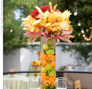 The patio tables were topped with cymbidium orchids in vases filled with submerged peppers and fruits.