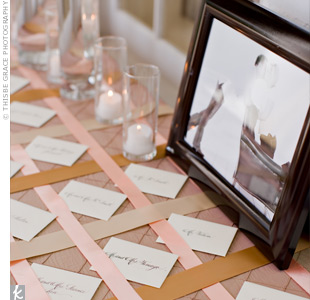 The escort cards for the rehearsal dinner were set on top of a table covered with amber linens and gold, peach, and chocolate-colored ribbon.