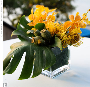 On outdoor cocktail tables, modern, square glass containers held a mix of tropical flora, like large monstera leaves, green poppy seedpods, yellow protea, and golden Mokara orchids.