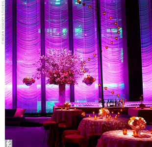 A circular display of tea lights hung from the ceiling down onto the tabletops. Large orchid spray arrangements framed the room.