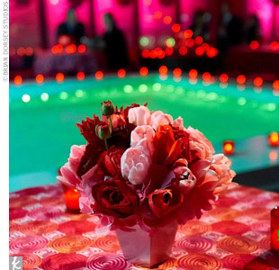 Tables decorated in a pink, orange, and red color scheme surrounded an indoor pond, which was created especially for the event. The tables were topped with pink and red tulip and rose arrangements.