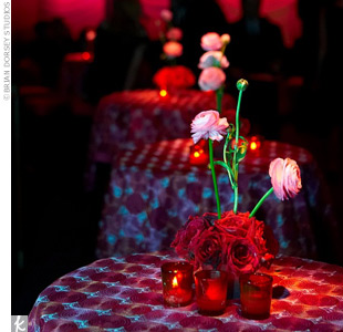 The red linen cocktail tables were topped with pink ranunculus bursting from a bed of red roses. Red votives with candles surrounded the arrangements, adding a soft glow to the space.