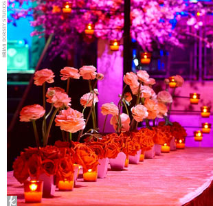 From beginning to end, pink and red abstract floral arrangements ran down the center of the long tables. A large tree decorated with colorful tea lights lit up the space and created a focal point.