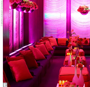 Purple-lit drapery and hanging vases of red and pink blooms defined the lounge space. Pink and red pillows were strewn across the cushy black sofa, and pink pashminas added a pop of color and were a fun accessory for the ladies.