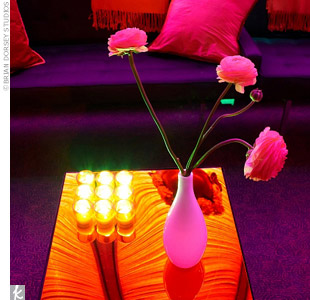 Tea light candles cast a glow on white vases overflowing with fresh pink ranunculus.