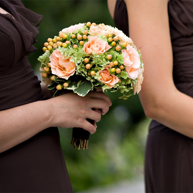 The bridesmaids bouquets of peach roses, berries and green hydrangeas stood out against their dark dresses.