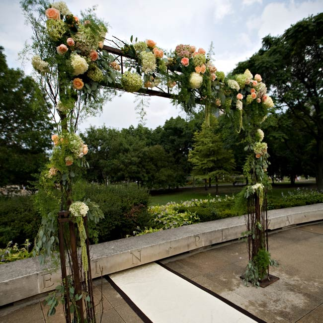 Stephanie and Scott exchanged vows beneath a wrought-iron arch. The flowers that decorated it, roses, hydrangeas and hanging amaranthus, coordinated with the bouquets and centerpieces.