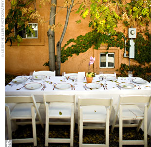 To focus guests' attention on the stunning location, the couple opted for minimal reception decor: white linens and chairs, and white plates rimmed with a rustic gold to match the color of the building's ivy-covered exterior. The tree shading the table enhanced a backyard picnic-like feel.