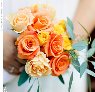 Lara originally wanted a bouquet of poppies or ranunculus, but they were out of season for her October wedding. Instead, she carried orange and yellow circus and spray roses accented with eucalyptus leaves for a similar warm, earthy feel.