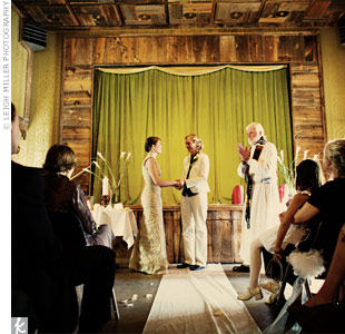 Built in the 1860s, the Pinos Altos Opera House is a treasure of the New Mexico hills, featuring a rustic, wood-paneled stage, lime-green curtains, and antique lime wallpaper. Anna and Amy added a white aisle runner and vases of white calla lilies, white tea candles, and giant red candles at the altar.