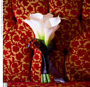 The bridesmaids carried all-white calla lily bouquets. Audrey walked down the aisle with a bouquet of fresh-cut red roses wrapped in ivory satin ribbon and a pearl necklace that belonged to her mother.