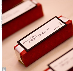 Audrey and Donny's escort cards doubled as favors. Audrey used red paper to wrap boxes filled with wine stoppers, then printed guests' names on ivory paper and mounted them to black card stock.