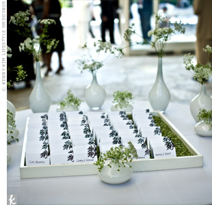 Escort cards sat on a bed of dried split peas inside a white-rimmed mirror. A black stamp decorated the upper right-hand corner of the tented cards and rhinestones added a touch of sparkle.