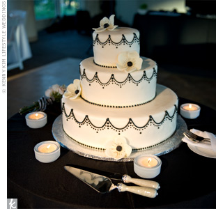 A black-and-white draped pattern and sugar anemones decorated the three-tiered cake.
