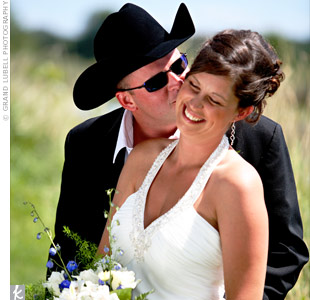A simple halter dress with a low-cut back, a straight skirt, and a sweep train was a fitting choice for the Western-themed wedding because of its laid-back look.