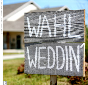 "Amy used some cedar wood she had on hand to make signs that directed guests to parking lots. She wrote ""weddin'"" instead of ""wedding"" to fit the country vibe."