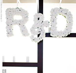 The couple's monogram made out of white roses hung in front of the bar area. White votives decorated the backdrop.