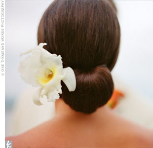 Nikki wore a fresh white orchid pinned in her hair for the reception. She had done a trial run a month beforehand to ensure she got this simple, chic hairstyle.