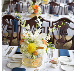 The reception tables were topped with fresh flower centerpieces filled with white orchids and hydrangeas and a mix of yellow and orange dahlias and mums. Orange slices lined the round vases to give it a fresh look.