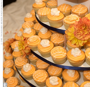 Michael loves cupcakes, so they decided to skip the traditional wedding cake idea. Their cupcakes were creamsicle-flavored, frosted in orange, and drizzled with white chocolate or topped with white chocolate roses.
