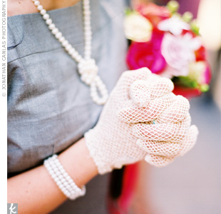 The bridesmaids' gray A-line dresses, lace gloves, and pearl jewelry maintained the wedding's elegant, vintage theme. Feathered headbands and gray high-heeled shoes completed the look.