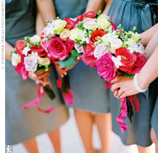 Red, pink, and yellow rose bouquets wrapped in raspberry ribbon created a colorful contrast to the bridesmaids gray dresses.