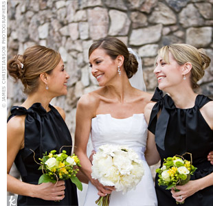 The bridesmaids' black satin Vera Wang cocktail dresses with grosgrain ribbons coordinated with the details of the day. For a burst of color, they carried bouquets of yellow roses and freesia, and green hypericum berries and Kermit mums.