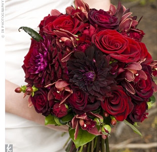 Velvety shades of red and purple made up Brooke's romantic bouquet of roses, dahlias and orchids. A blue ribbon tied the blooms together at the stems.