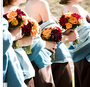 The ladies wore coordinated brown Ann Taylor dresses with blue taffeta and wool wraps, made by one of the bridesmaids. The bouquets were filled with orange roses and burgundy dahlias for a colorful twist.