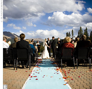 The bride and groom both grew up around the mountains, so they wanted to incorporate the majestic backdrop into their wedding day. The gorgeous view and a hand-painted blue aisle runner sprinkled with red and orange rose petals made up the décor.