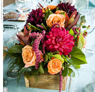 To play up the rustic elegance theme, blue table cards edged in a brown floral print were tucked into wooden boxes with fall foliage-colored roses, dahlias, amaranthus, leucadenron and hypericum berry accents.