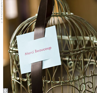 "A vintage birdcage provided the perfect resting place for cards. Blue ribbon and a Kraft paper tag that read ""Merci beaucoup"" or ""thank you"" in French, personalized the cage"