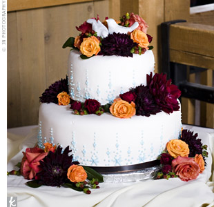 Songbird salt-and-pepper shakers brought the couple's theme to the top of their two-tiered wedding cake. Fresh fall flowers, blue icing and brown ribbons detailed the fondant-covered confection.