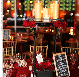 Wrought iron pedestals were topped with candle in varying heights and decorated with red roses and real grapes. Custom-designed chalkboard menus added a playful touch to the tables cape.