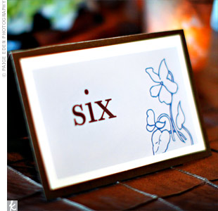Bold chocolate brown table numbers stood out on the custom blue motif cards and brown matte board.