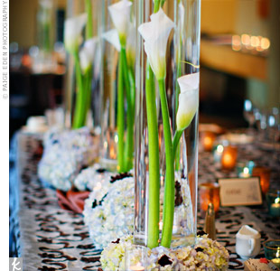 Calla lilies submerged in tall cylindrical vases complemented the modern architecture of the space. Blue hydrangeas and chocolate cosmos surrounded the base of each centerpiece, reflecting the couple's color scheme.