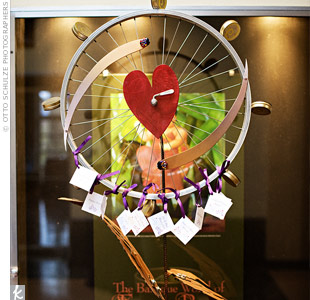 Tracy and Paul found the perfect element for their escort card display -- a bicycle wheel with a heart in the middle. Each card was hung from the rim with purple satin ribbon.